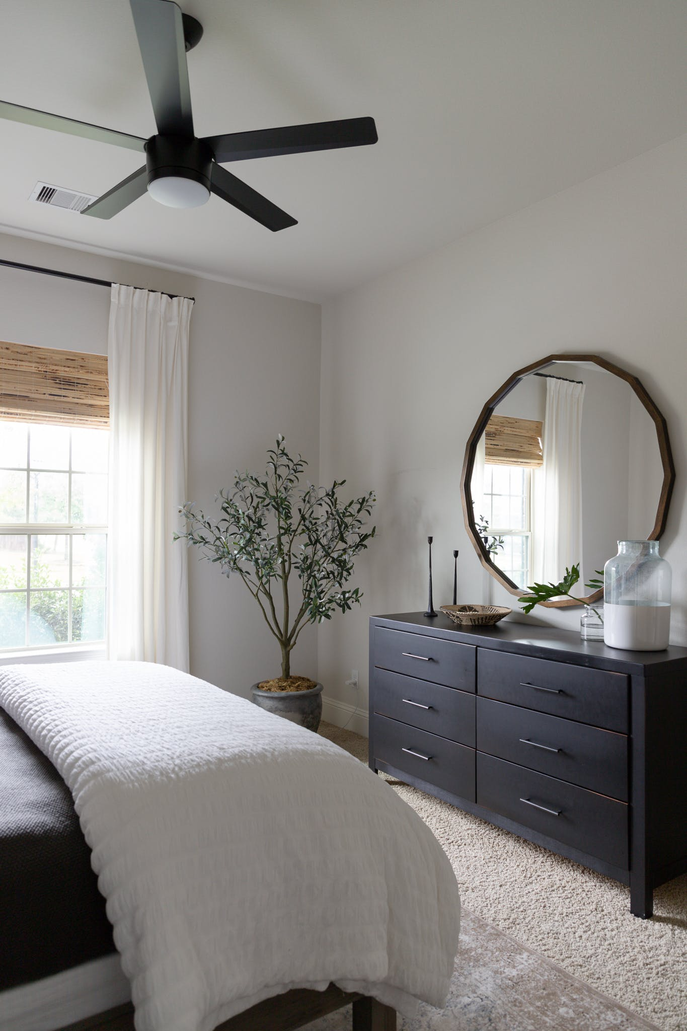 guest bedroom with woven wood shades and white curtains