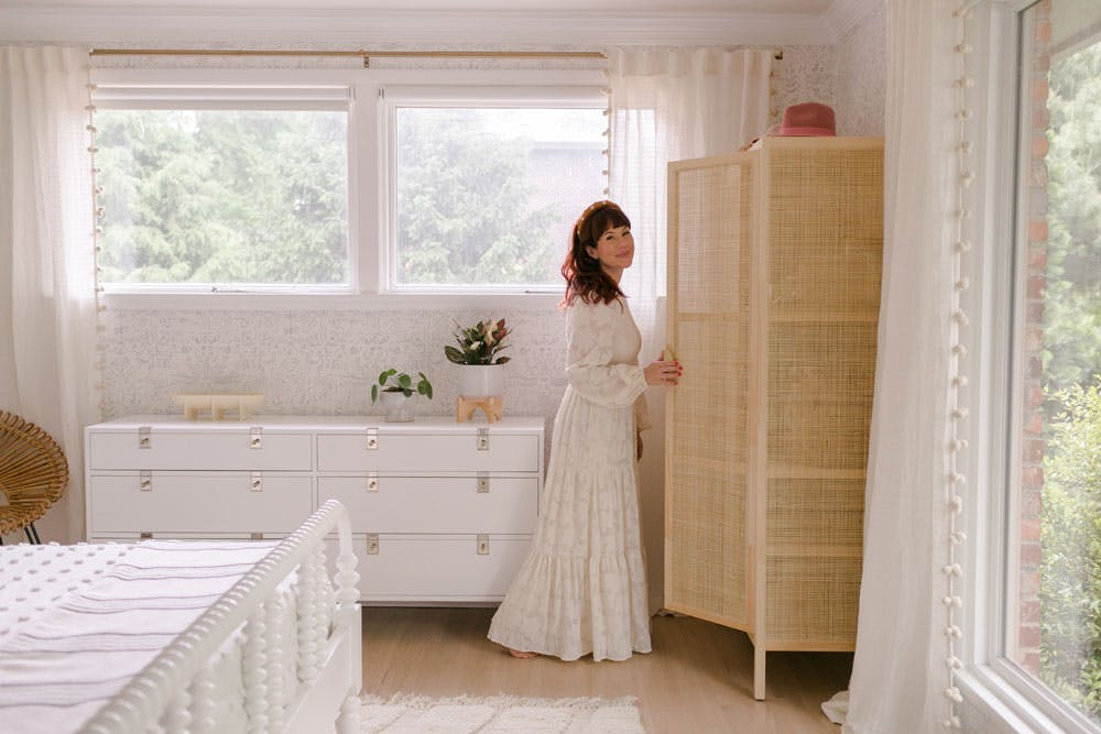 woman in white dress opens cabinet in neutral bedroom with blackout shades