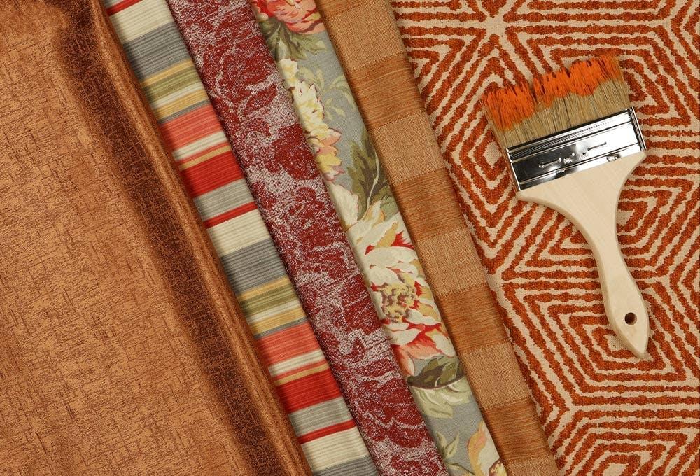 flatlay with burnt orange drapery samples and orange paintbrush.