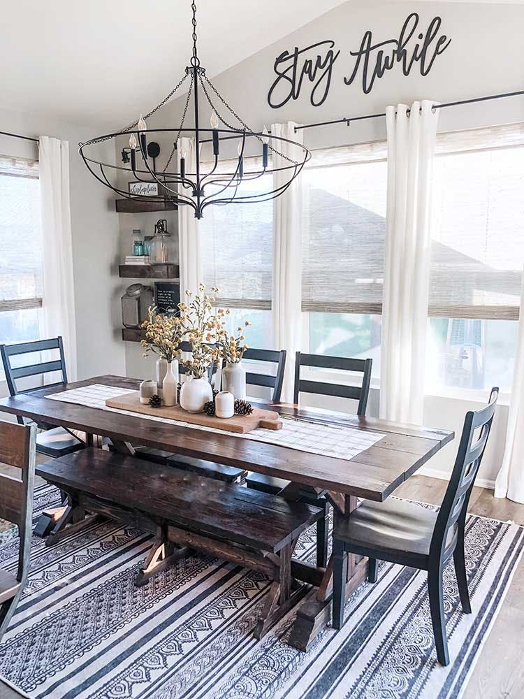 modern farmhouse dining room table with woven wood shades over windows.