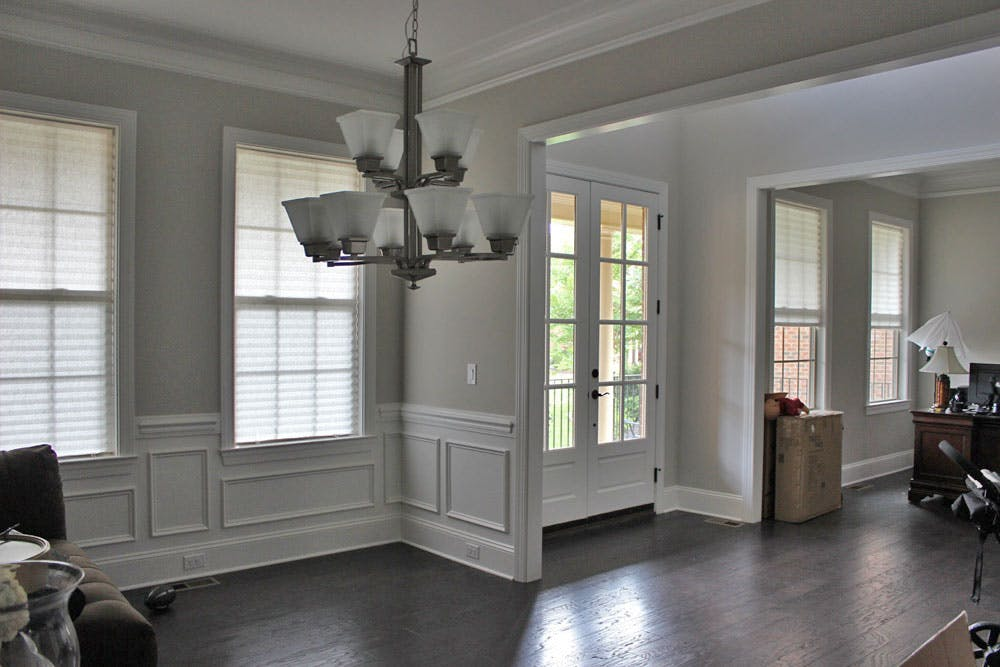 spacious, open concept living and dining room with two windows covered with cellular shades on each side of the french doors (which are not covered with shades).