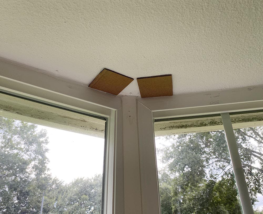 two small cardboard squares taped above a window to aid in measuring.