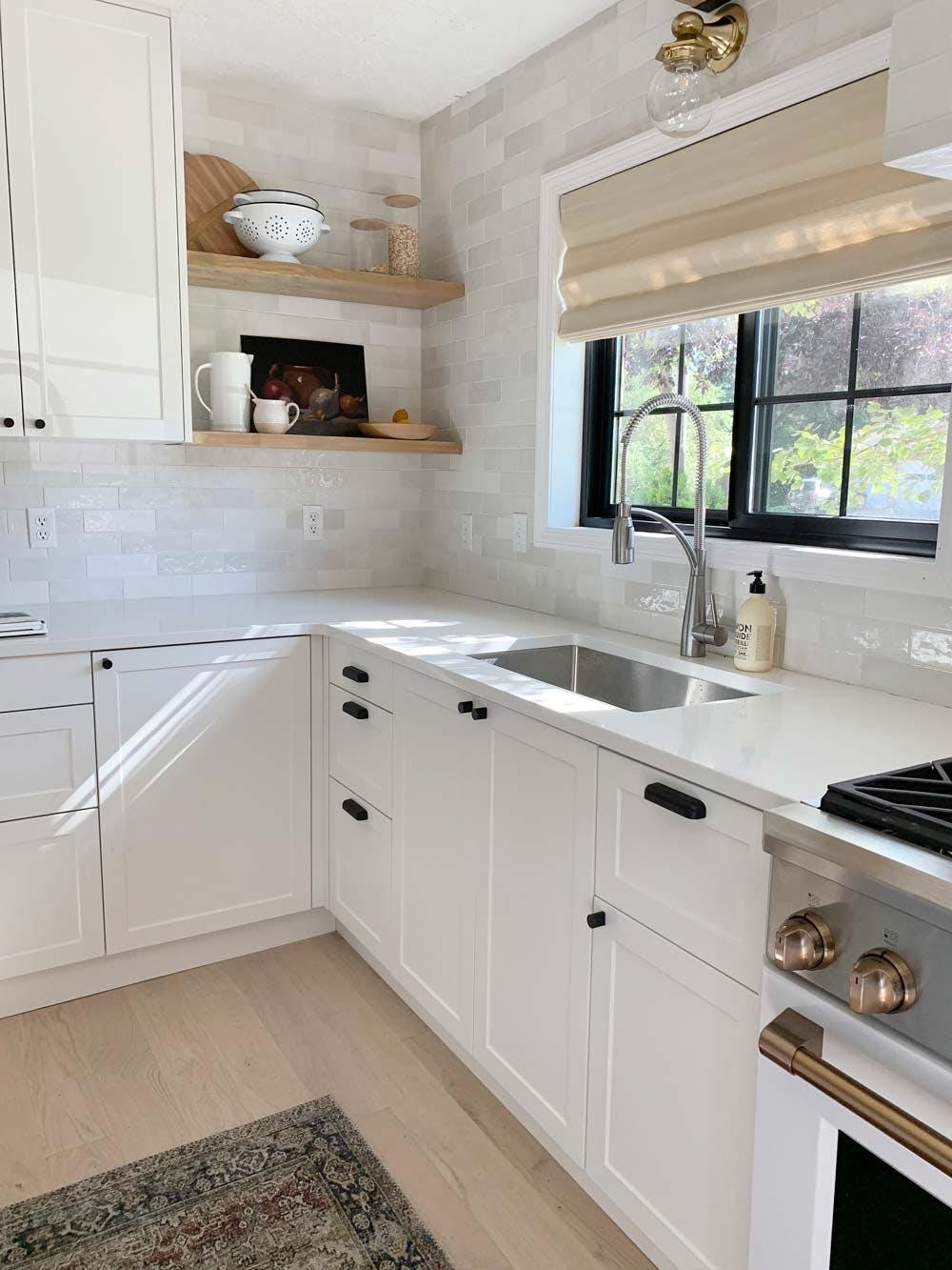 window behind kitchen sink with light beige woven shade