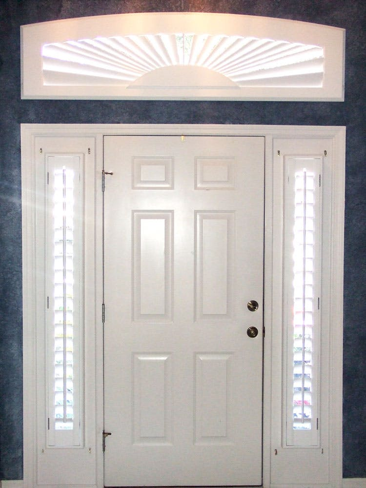 Front door with shutters of the sidelights on each side and over the arch window above the door.