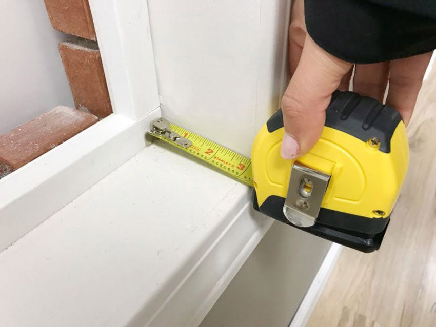 A tape measure held against a window to measure it's depth from front to back.