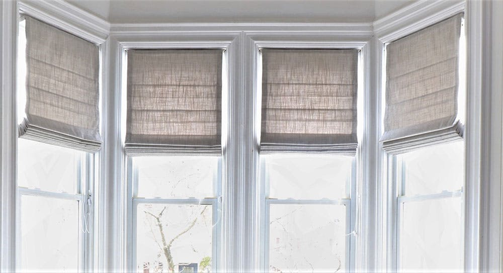 a bay window with partially recessed inside mount roman shades in a gray linen.