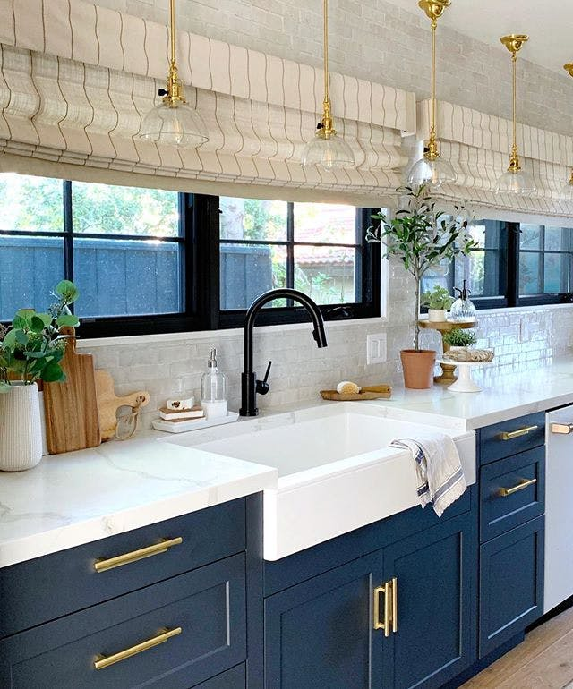 traditinoal kitchen with blue lower cabinets and linen roman shades on long bank of windows