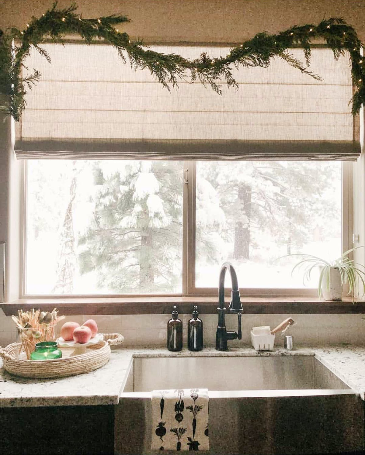 Kitchen sink window with forest view and a roman shade partially lowered.
