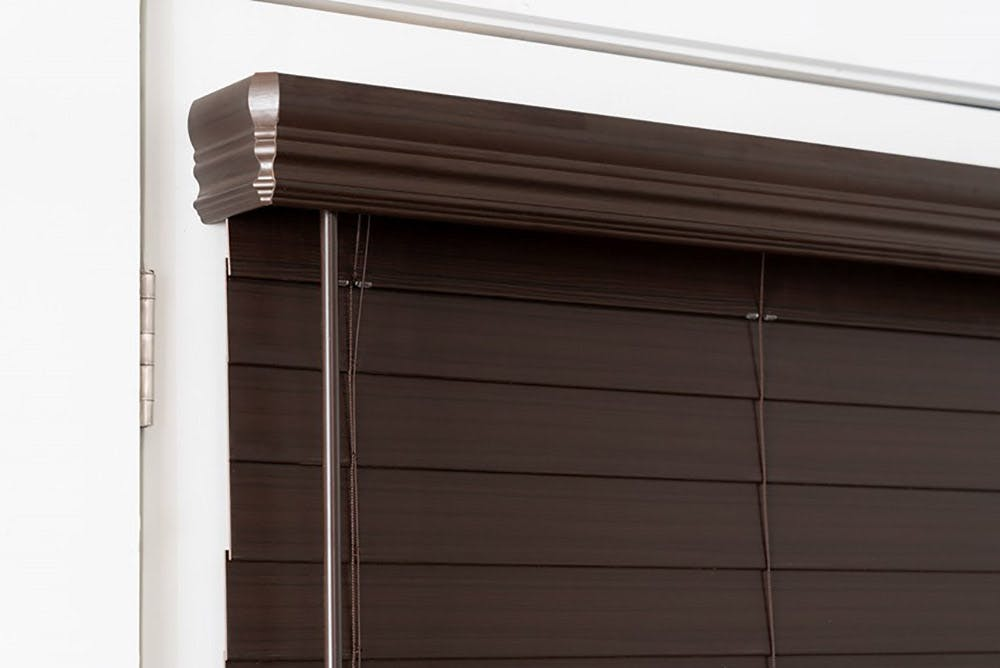 close up of a dark brown faux wood blind with a valance that wraps around the sides.