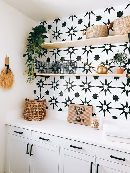 laundry room storage cabinets with patterned tile wall and floating shelves
