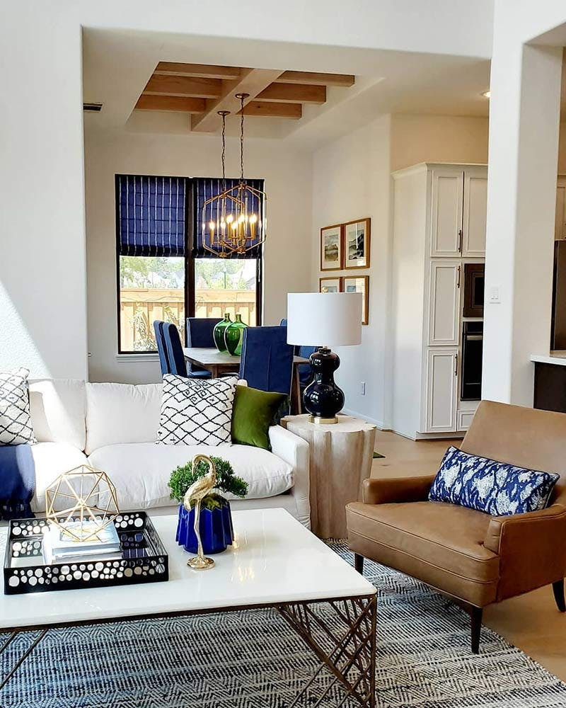 contemporary living room with blue throw pillow, roman shade and other accents.