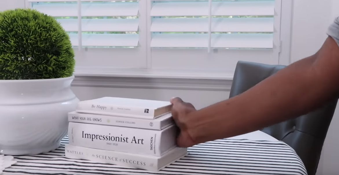 woman creating centerpiece with books in front of white window shutters
