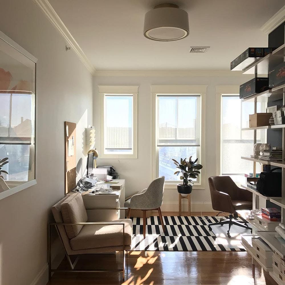 Modern, sunny living room overlooking a city skyline. Solar shades are lowered over the windows.
