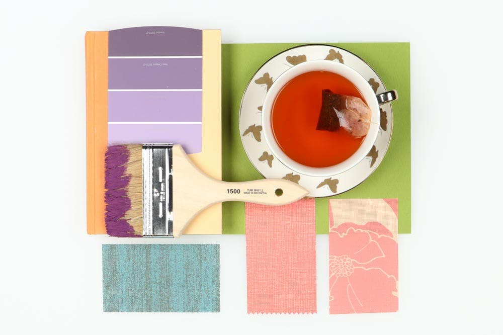 colorful flatlay with teacup, solar shade samples and paint brush.