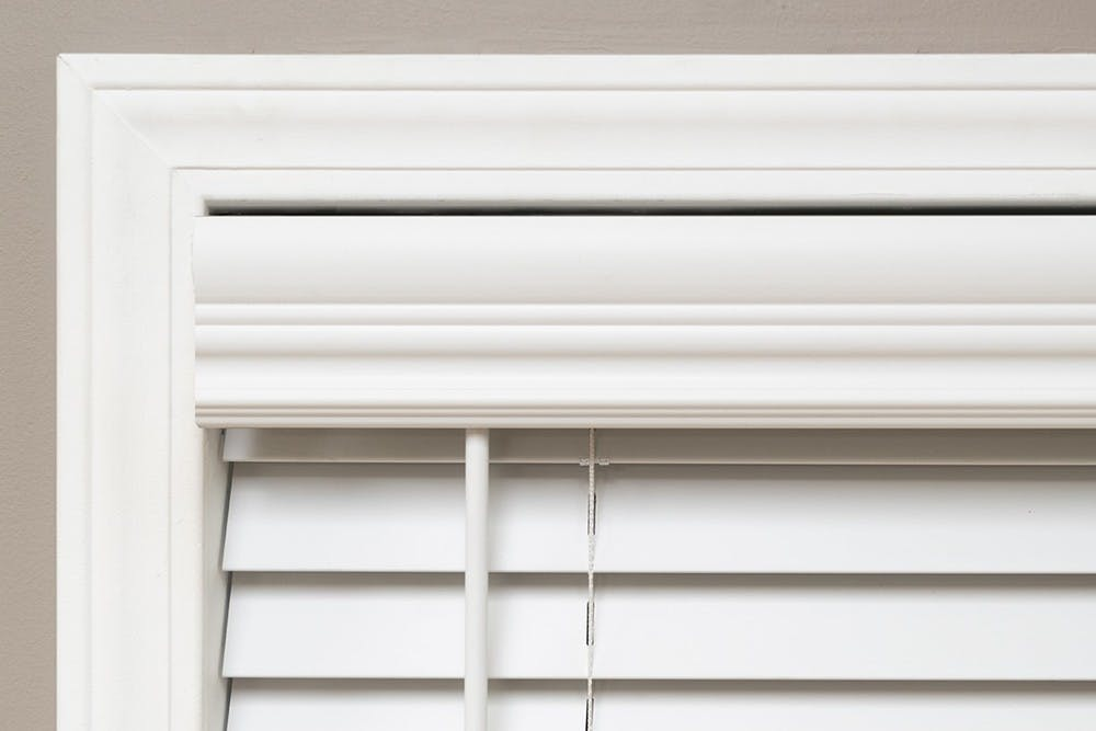 Close up image showing the decorative valance details and standard tilt wand on the Economy Cordless Faux Wood Blind.