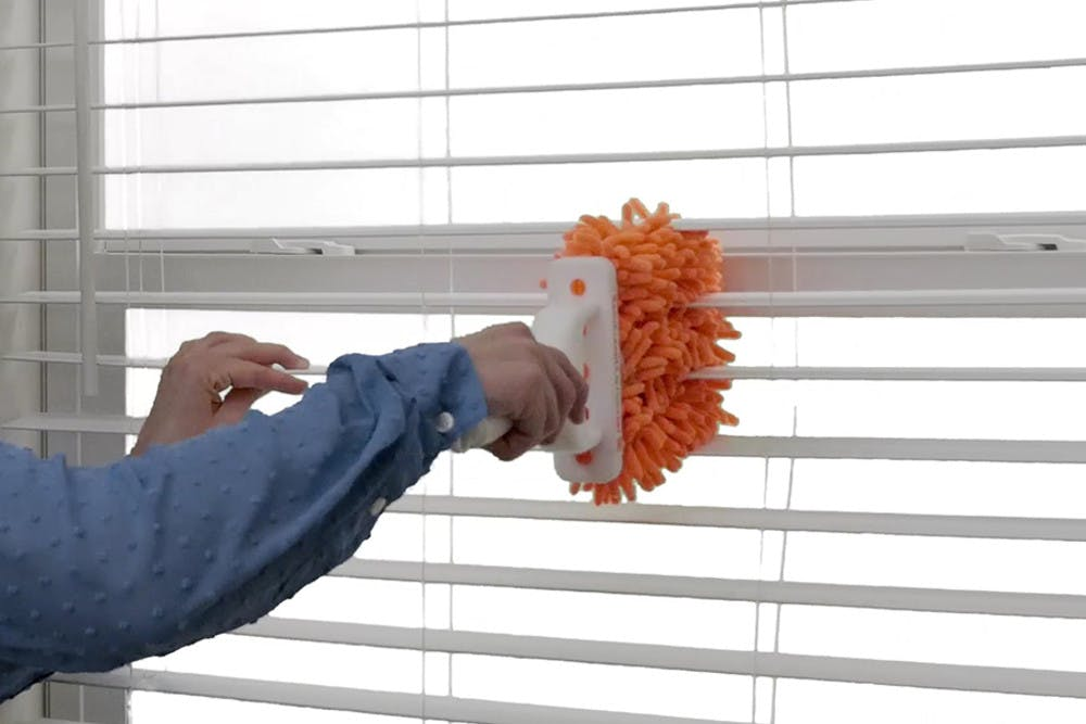 Orange microfiber duster deisgned to clean in between window blind slats, three at a time.