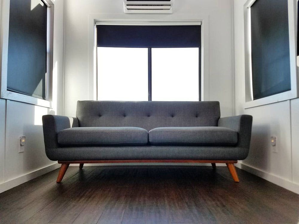 modern mobile home with blackout shades and midcentury sofa