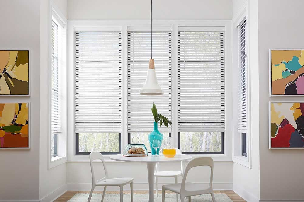 A bright, modern dining room with cordless white faux wood blinds with juice and biscuits on a table set for two.