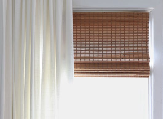 closeup of woven wood shades with white curtains