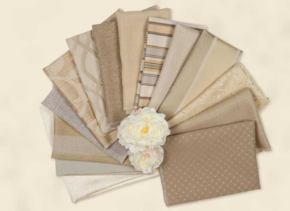 Beige fabric samples fanned out in a flatlay.