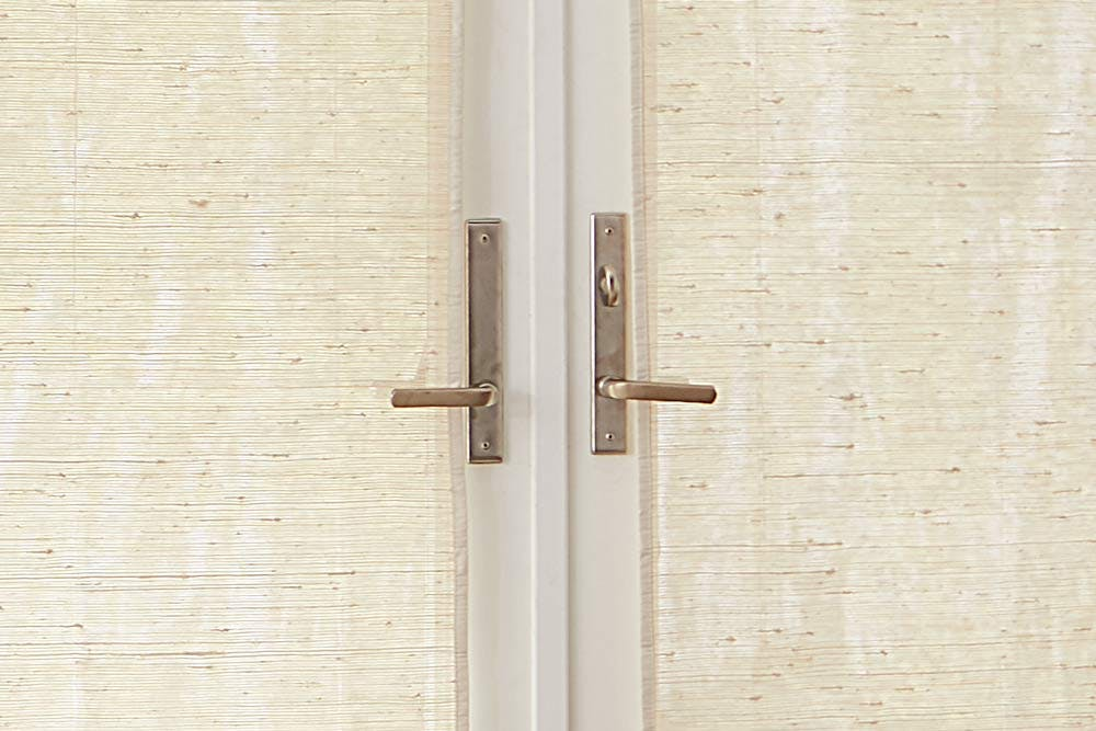 close up of woven wood shades passing behind french door handles.