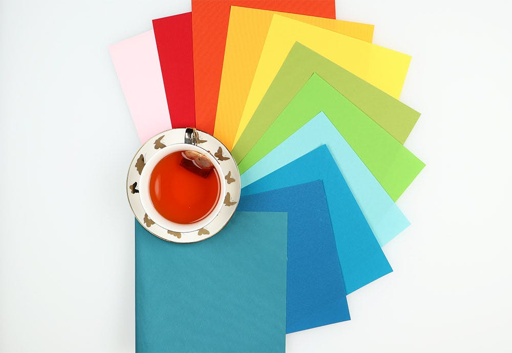 vinyl fabric samples in rainbow order around a white and gold tea cup.