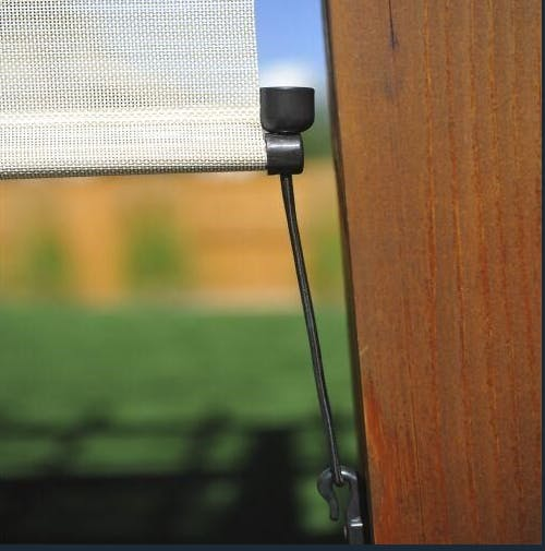 close up of a tie down being used to anchor the bottom of an outdoor solar shade.