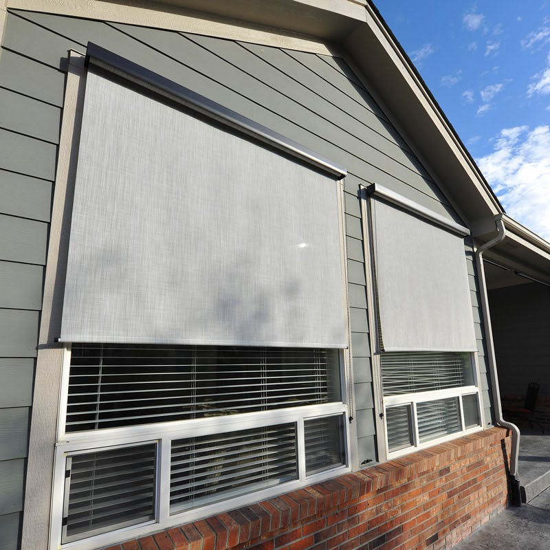 outdoor shades installed over windows to save energy