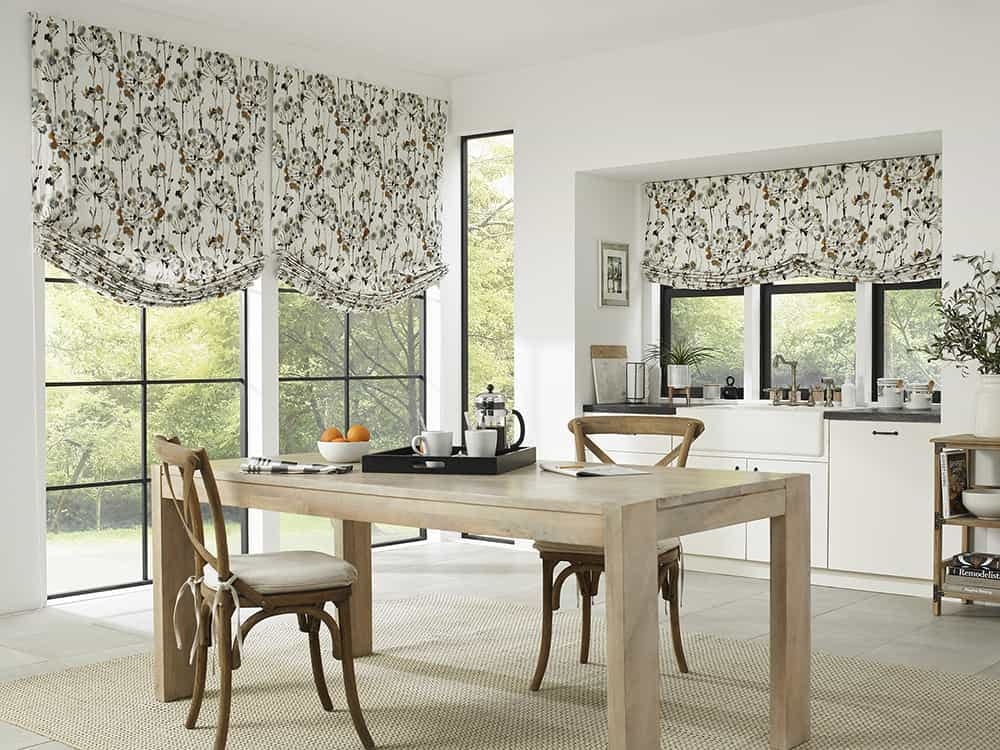 Open, modern kitchen and dining room with floral roman shades over the tall windows.