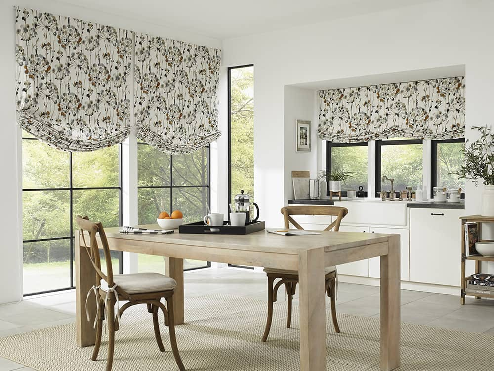 modern kitchen with floor to ceiling windows and floral roman shades