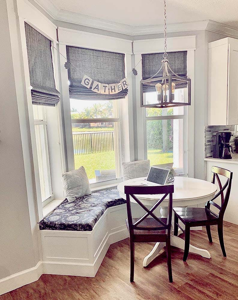 dining room bay window with cushioned window seat and grey linen roman shades.