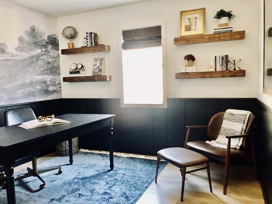 home office with scenic valley wallpaper, wood accents and black board and batten trim on the lower half of the walls.