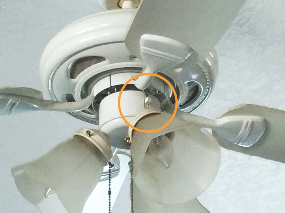 close up of a ceiling fan's motor housing showing where a direction switch may be located.