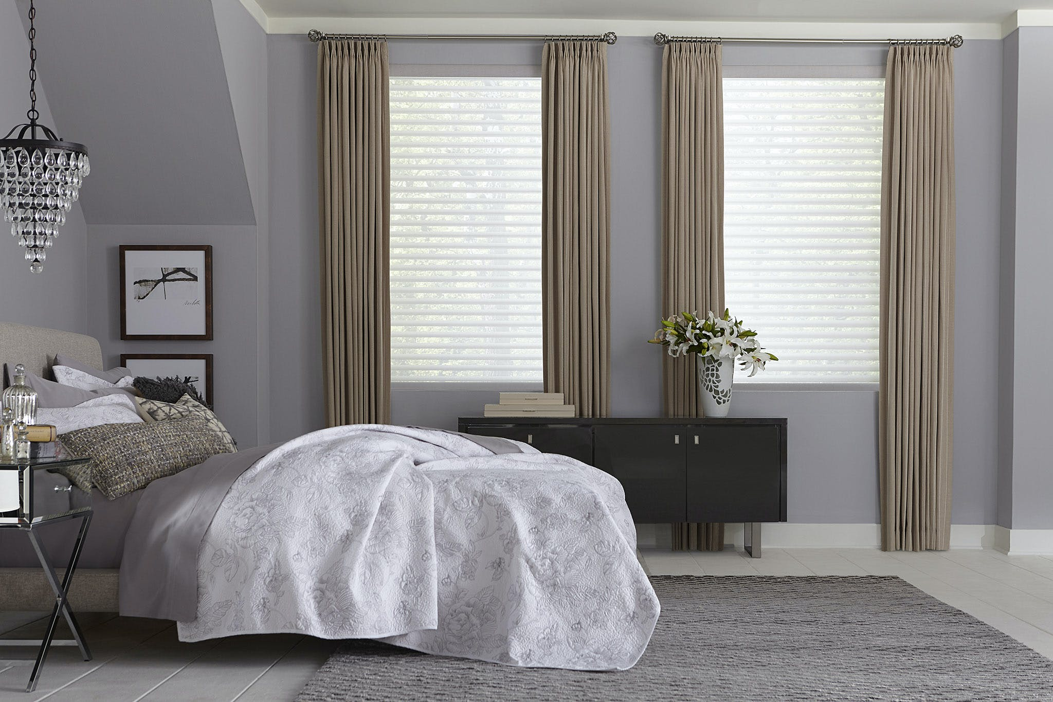 Traditional bedroom with blackout curtains draped over light filtering sheer shades.