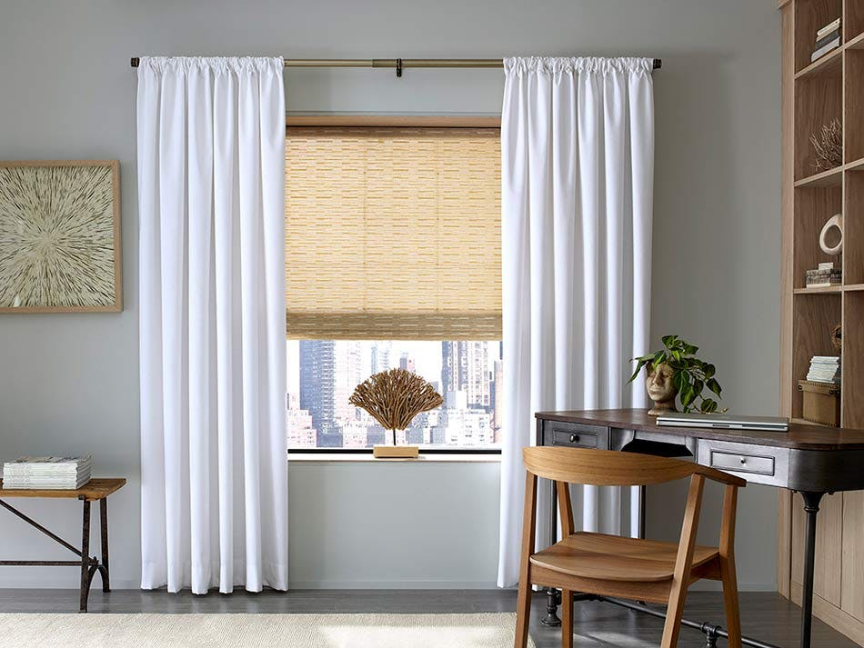 Transitional styled office with woven wood shades and white drapes.