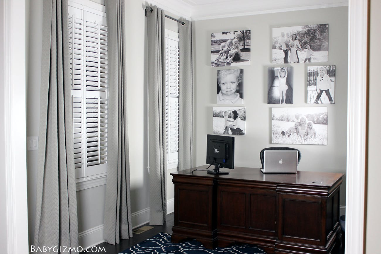 Grey office with large wood desk, grey drapes and a wall of black and white family portraits.