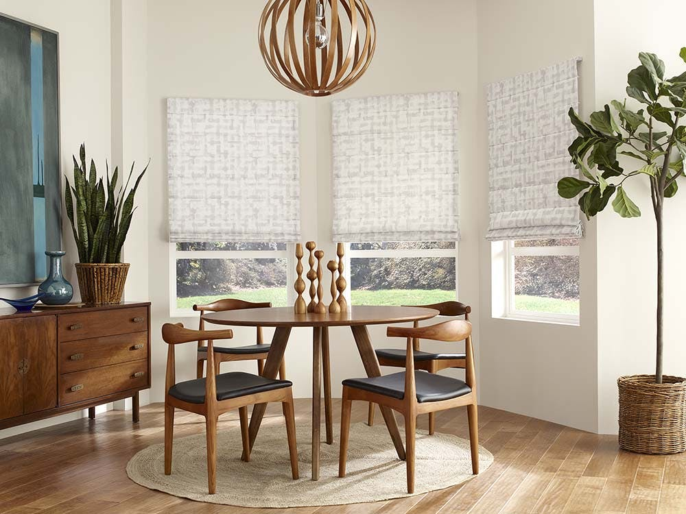 a midcentury modern dining room with a bay window covered with roman shades.