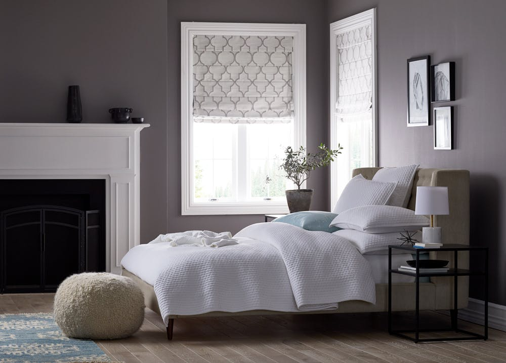 Contemporary bedroom with grey walls, white bedding and blackout roman shades in the windows.