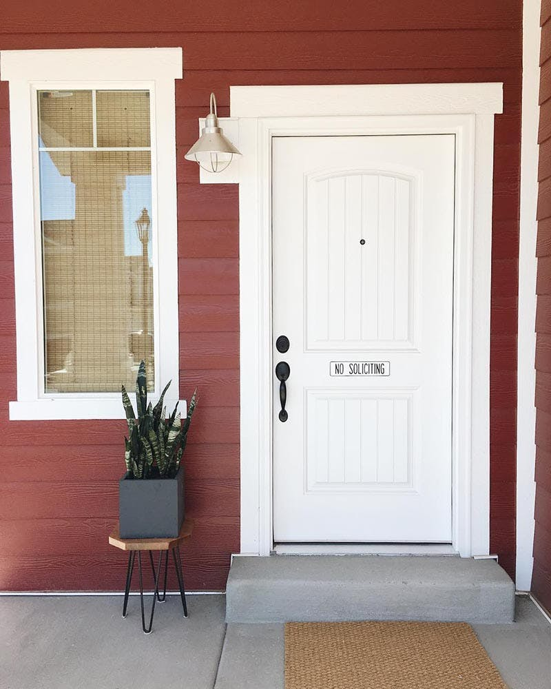 White front door of red home with window and woven wood shade fully lowered.