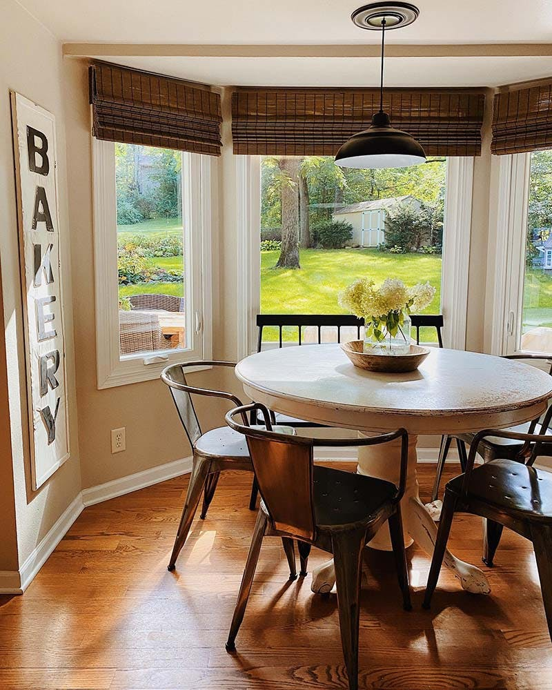 bright, sunny, modern farmhouse dining room with a bay window and woven wood shades.