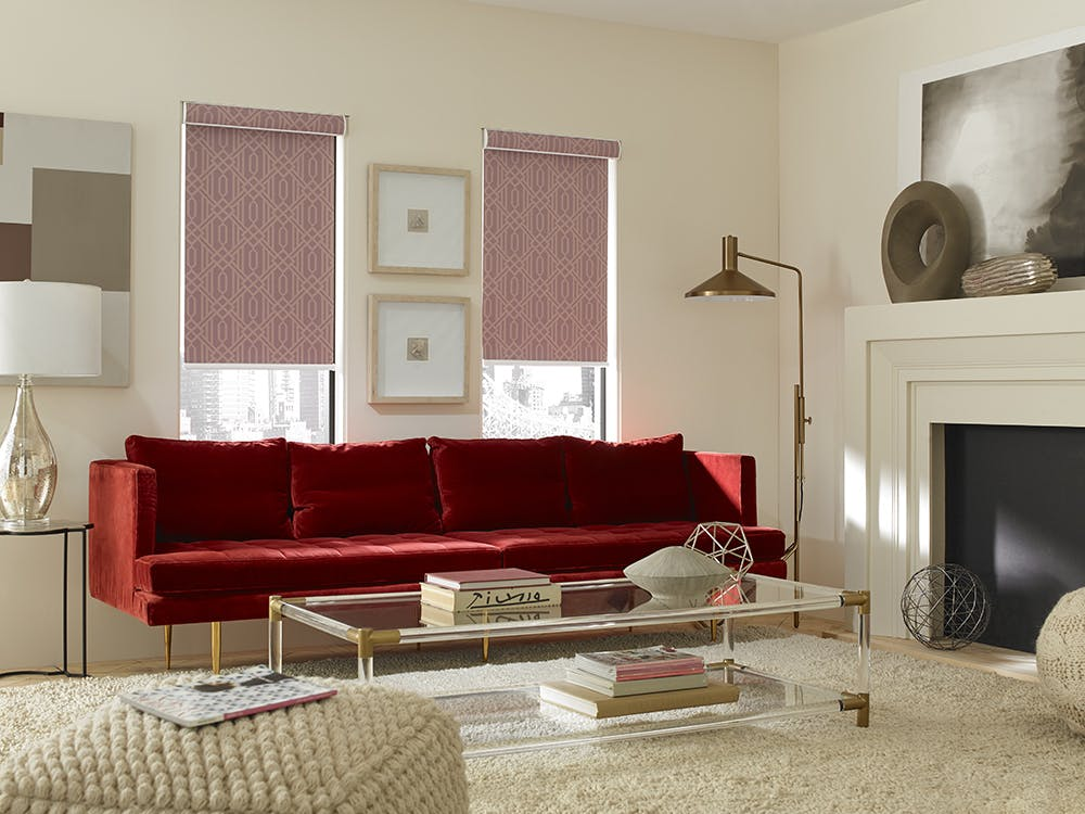 Living room with red couch and The Economy Blackout Fabric Roller Shades in Deco Persimmon.