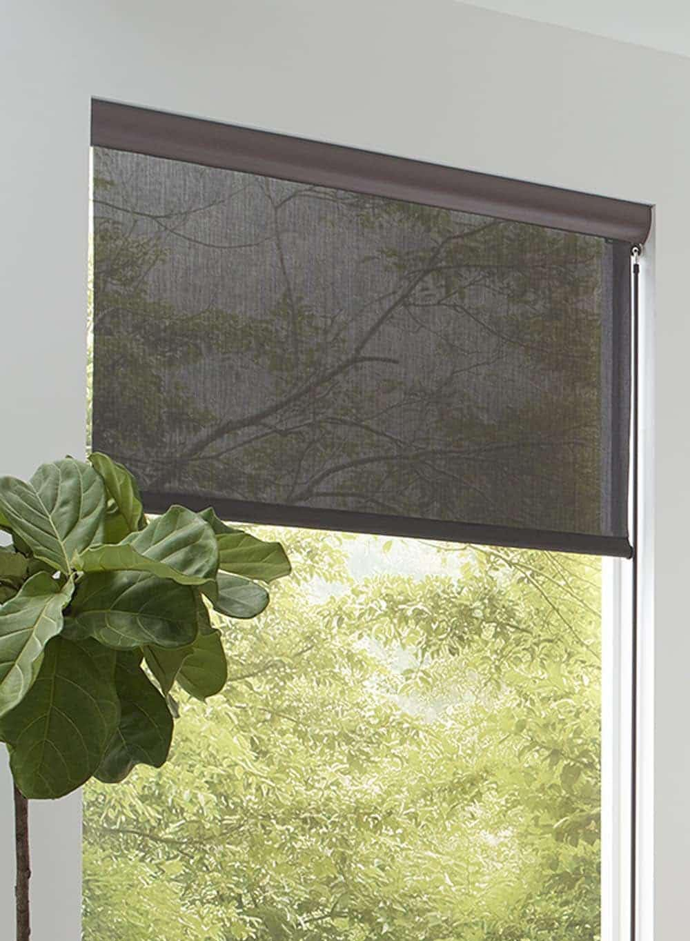 A dark brown outdoor shade partially lowered in a window of a covered patio area.