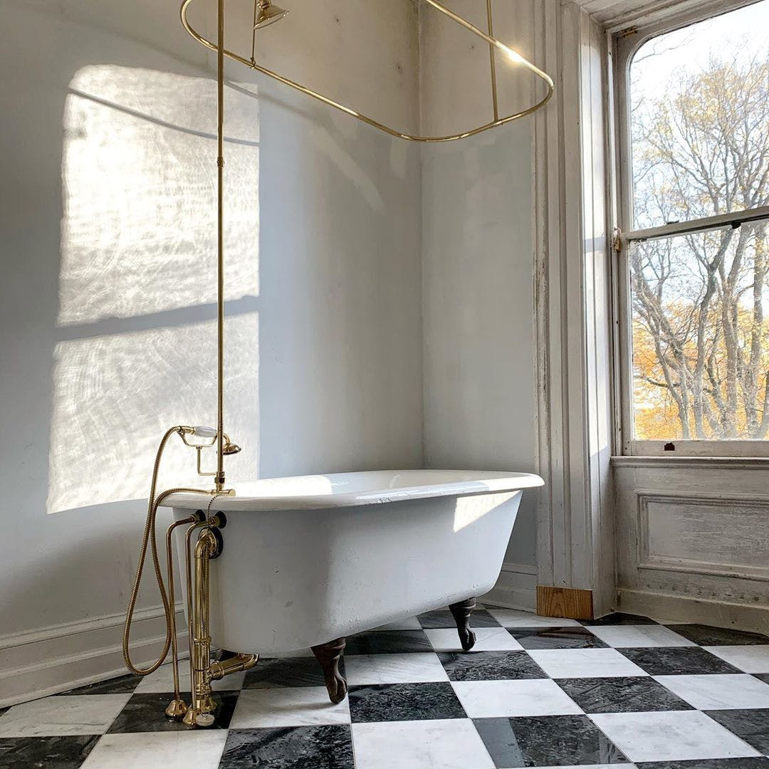 bathroom with checkered floor and oversized freestanding tub.