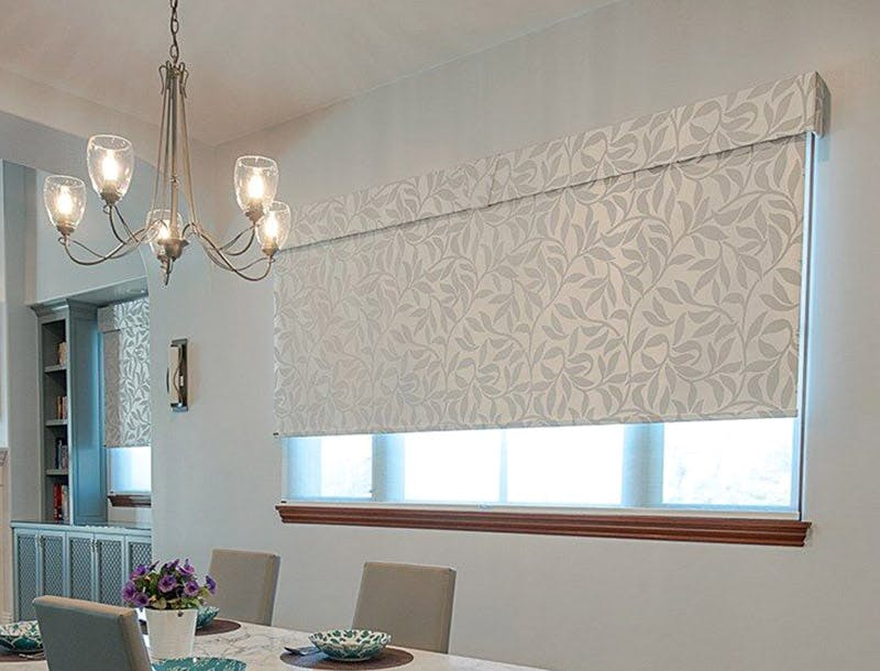 kitchen dining table near a large window covered with a white, leafy print roller shade.
