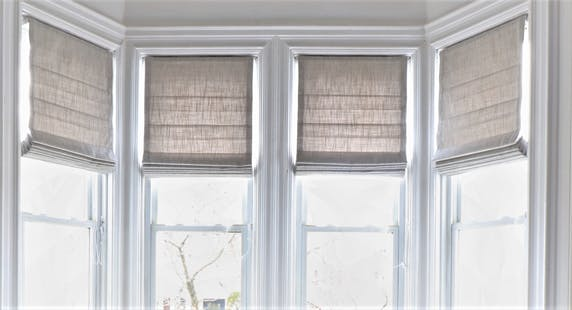 Closeup of linen roman shades in bay window