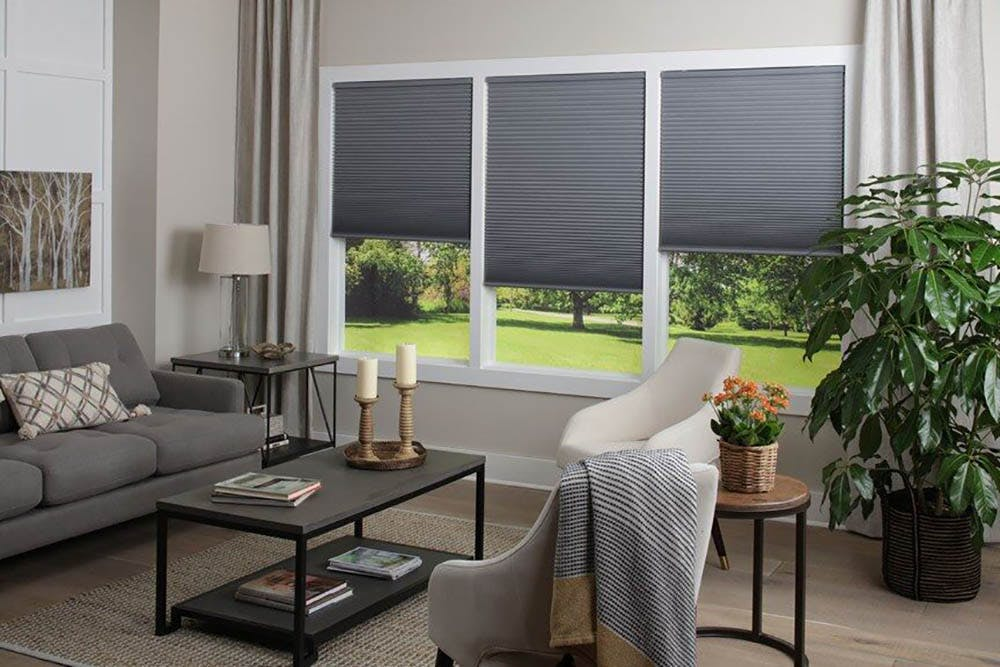 a contemporary living room with gray cellular shades of the windows.