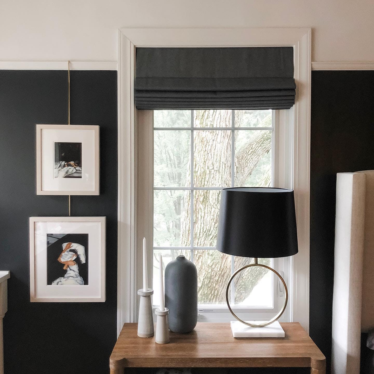 Wood bedside table in front of a window with a black wall and dark slate colored roman shade.