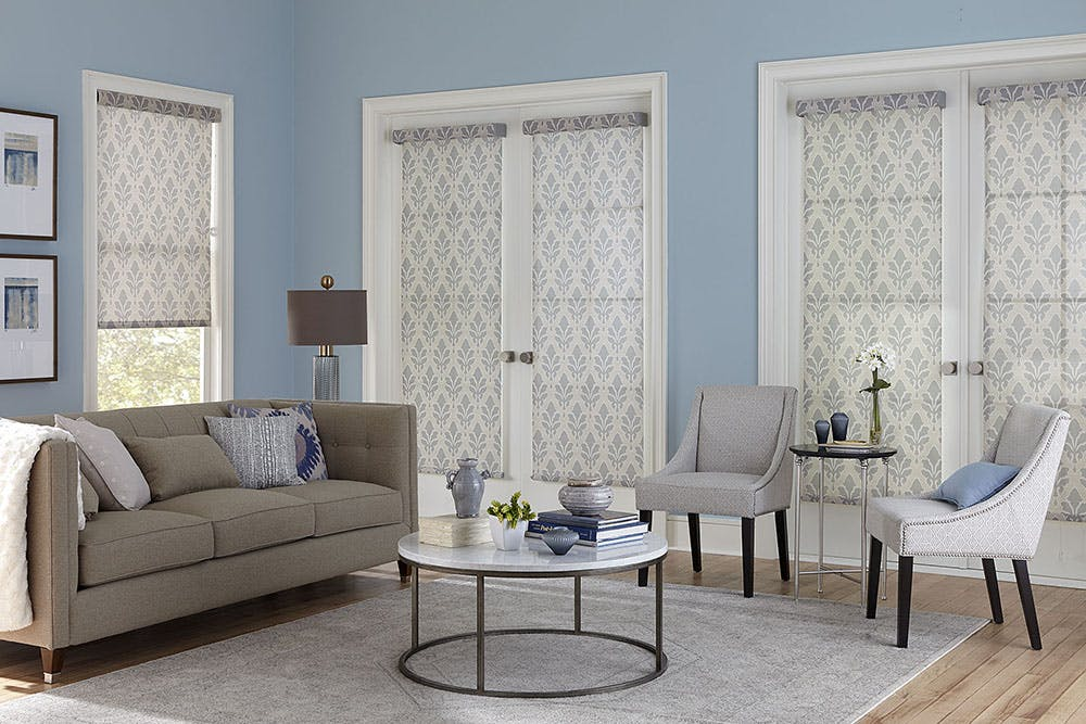 bright, contemporary living room with baby blue walls and damask printed, gray solar shades over the french doors and windows.