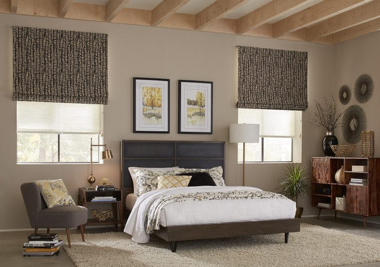 bedroom with brown roman shades and sheer roller shades