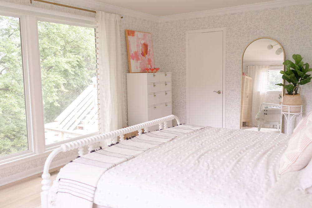 white bedroom with large picture windows and blackout motorized shades